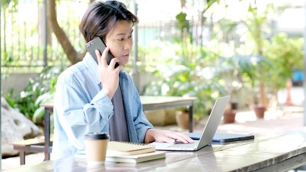 Trabajar desde casa feliz joven asiático mediante teléfono móvil en la oficina en casa