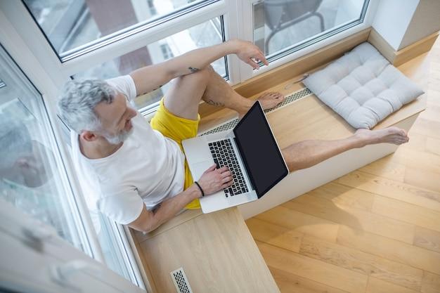 Trabajar desde casa. un hombre con una camiseta blanca sentado con una computadora portátil y trabajando