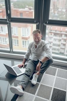 Trabajar desde casa. un hombre con una computadora portátil sentado en el suelo y trabajando en una computadora portátil