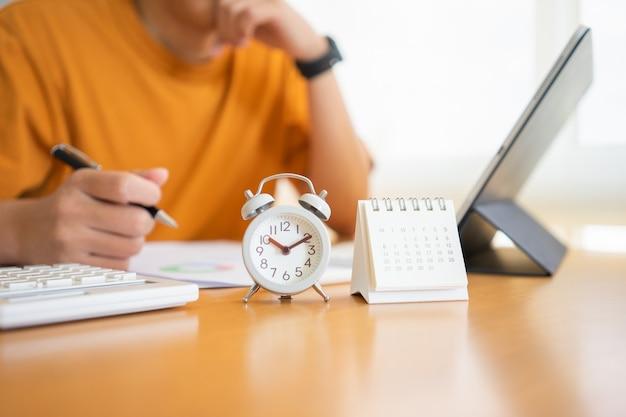 Trabajar desde casa joven independiente o empresario que trabaja en la oficina en casa con la tableta del teléfono inteligente. trabajando