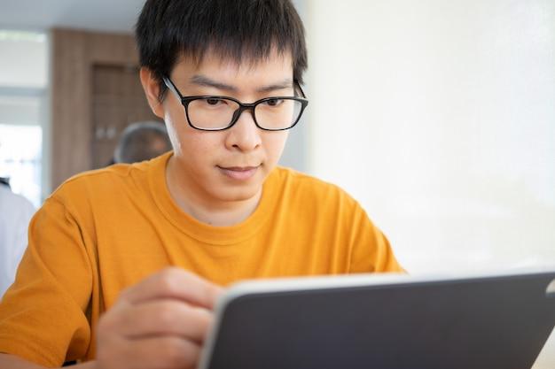 Trabajar desde casa joven independiente o empresario que trabaja en la oficina en casa con la tableta del teléfono inteligente.