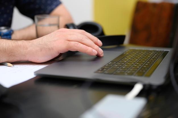 Trabajar desde casa. lugar de trabajo con una computadora portátil, auriculares, vaso de agua y papel para notas. hombre trabajador. mano masculina con un touchpad portátil.
