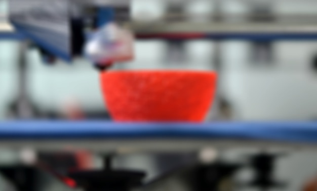 Trabajar cerca de la impresora 3d. impresión de la impresora 3d objeto plástico naranja sobre fondo azul. filamento de alambre de plástico, tecnología de impresión moderna. tecnología aditiva progresiva