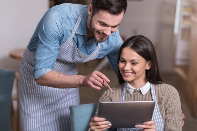 Trabajar juntos. inspiró alegre pareja de propietarios de café sonriendo y usando tableta mientras descansa.