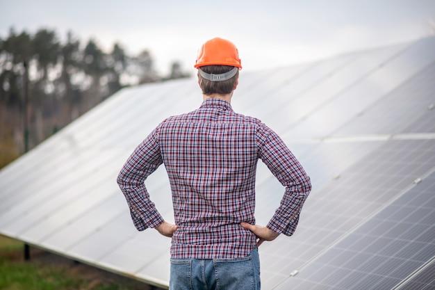 Trabajar, revisar. hombre con casco protector en camisa a cuadros de pie de espaldas a la cámara mirando la superficie de la estructura especial al aire libre