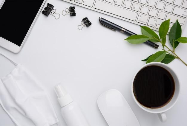 Trabaje desde el concepto de hogar con computadora portátil, máscara, taza de café, bolígrafo, teléfono en la pared blanca, plano