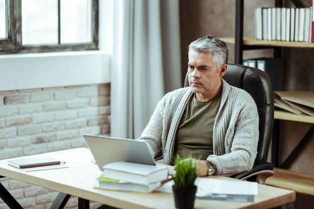 En el trabajo. agradable hombre serio mirando la pantalla del portátil mientras está en el trabajo