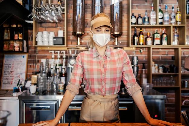El trabajo de un bartender en el momento de la corona. retrato de una persona de sexo femenino con una máscara de pie en un bar y con una mascarilla. espera pedir café o cócteles durante el covid 19.