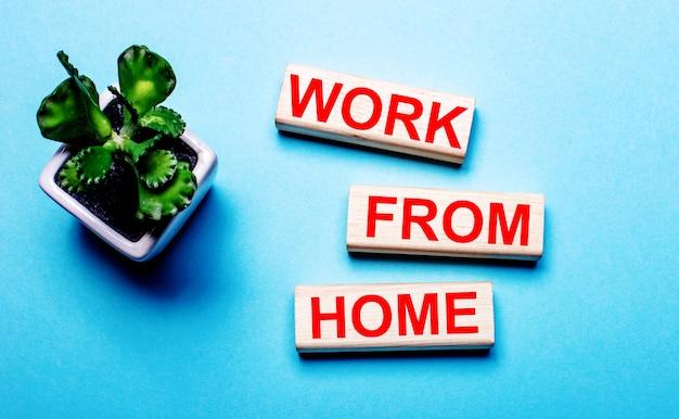 Trabajo desde casa está escrito en bloques de madera sobre un fondo azul claro cerca de una flor en una maceta