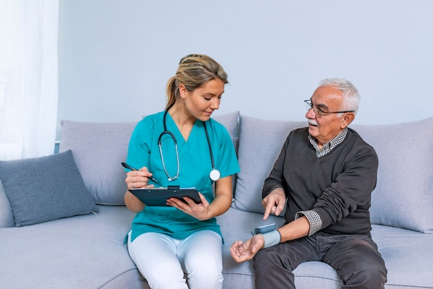 Trabajo del corazon cuidador atento que usa tonómetro mientras el anciano tiene problemas para respirar