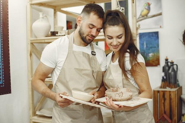 Trabajo creativo mutuo. hermosa joven pareja en ropa casual y delantales. la gente tiene platos de cerámica.