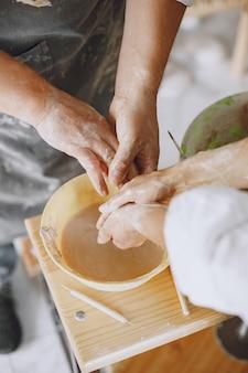 Trabajo creativo mutuo. pareja adulta elegante en ropa casual y delantales. personas creando un cuenco en un torno de alfarería en un taller de arcilla.