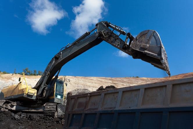 Trabajo de retroexcavadora amarilla en la mina de carbón