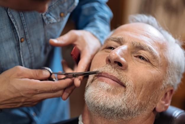 Trabajo delicado. cerca de buen hombre mayor con su bigote cortado por peluquero en barbería.