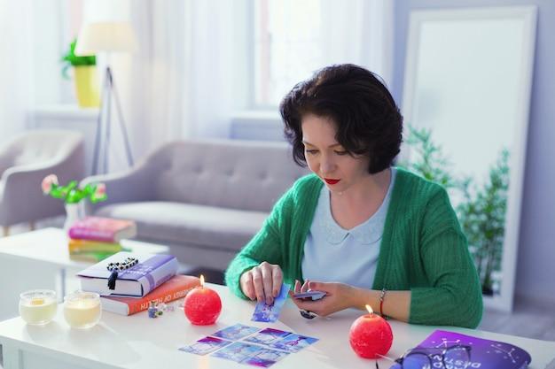 Trabajo dificil. adivino profesional inteligente mirando las cartas mientras interpreta su significado