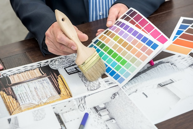 Trabajo de diseñador de interiores con boceto de apartamento, paleta de colores, computadora portátil en el escritorio de oficina. proyecto de plano de la casa