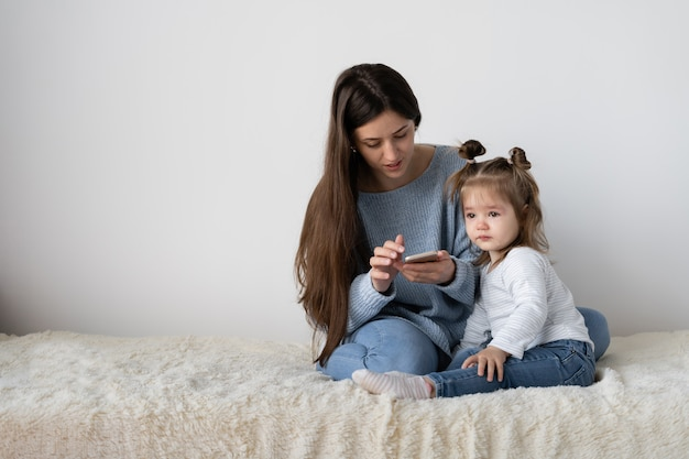 Trabajo a distancia en casa. mamá se sienta en el sofá y trabaja en el teléfono. cerca, una niña pequeña está llorando. no hay tiempo para los niños. la complejidad del trabajo a distancia. lugar para el texto