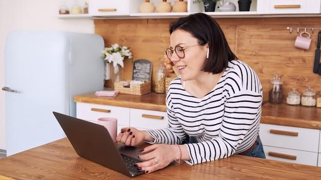 Trabajo a distancia. estudiante independiente usar auriculares estudiar en línea con el maestro. estudiar en una computadora portátil en casa.