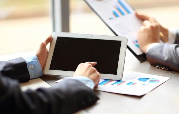 Trabajo de dos jóvenes empresarios con touchpad en reunión