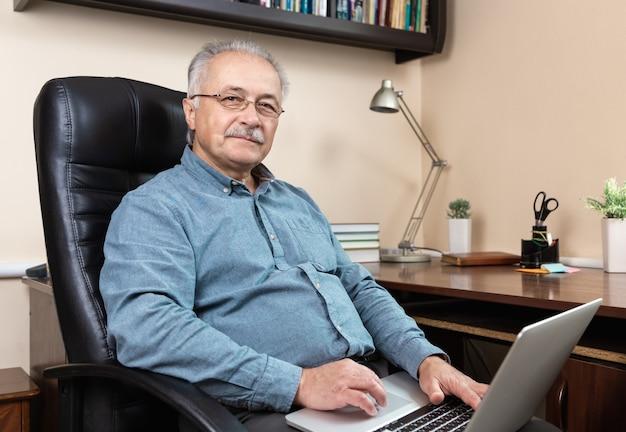 Trabajo de empresario senior en casa. un anciano con gafas está trabajando de forma remota con una computadora portátil. trabajo remoto durante el concepto de coronovirus