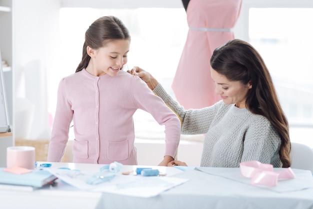 Para el trabajo. encantado de agradable mujer atractiva sonriendo y usando una cinta métrica mientras mide el tamaño de la ropa de sus hijas