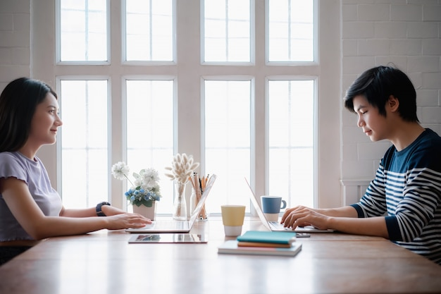 Trabajo en equipo asiático joven discutiendo juntos y escribiendo en la computadora durante el día laboral en la oficina en casa