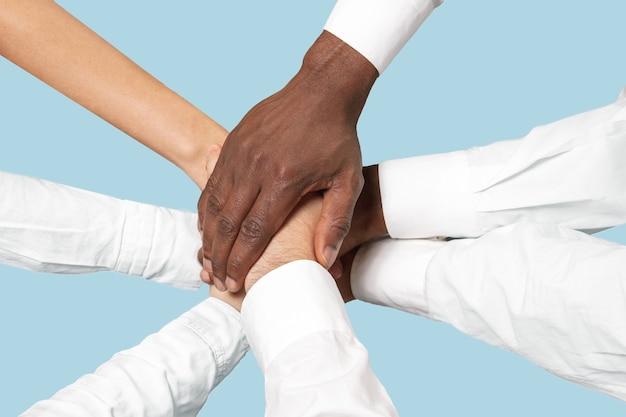 Trabajo en equipo y comunicaciones. manos masculinas y femeninas sosteniendo aisladas sobre fondo azul.