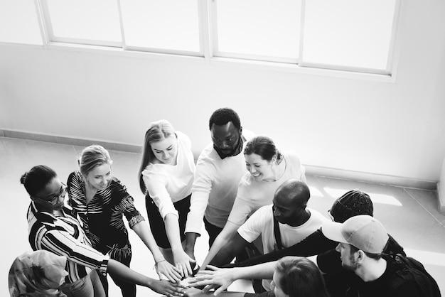 Trabajo en equipo de diversidad con manos unidas