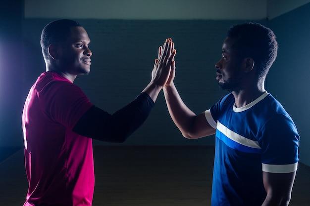Trabajo en equipo dos apuesto deportista afroamericano en boxeo sobre un fondo negro en el gimnasio, entrenador y sala practicando boxeo