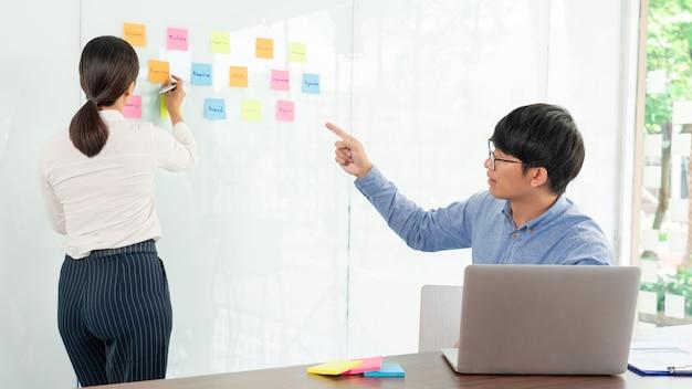 Trabajo en equipo empresarial en reunión y nota adhesiva en tablero de espejo discutiendo con el equipo en la sala de la oficina para recopilar algún plan de intercambio de ideas.