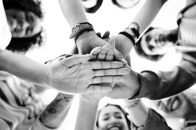 Trabajo en equipo de los estudiantes universitarios que apila concepto de la mano