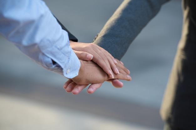 El trabajo en equipo de gente de negocios junta las manos.