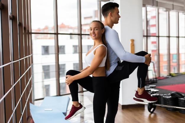 Trabajo en equipo de hombre y mujer en clase de fitness