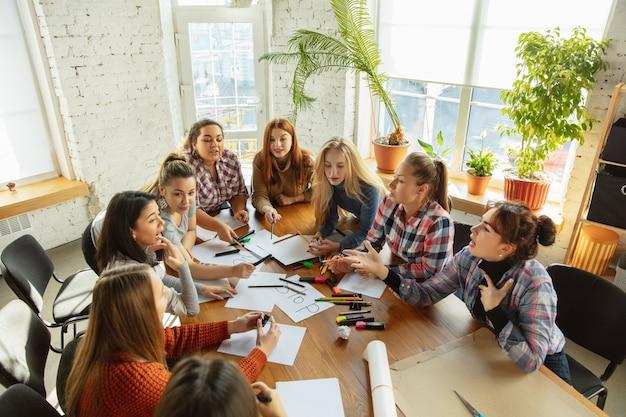 Trabajo en equipo. jóvenes discutiendo sobre los derechos de la mujer y la igualdad en la oficina. empresarias u oficinistas caucásicos se han reunido sobre problemas en el lugar de trabajo, presión masculina y acoso. Foto Premium