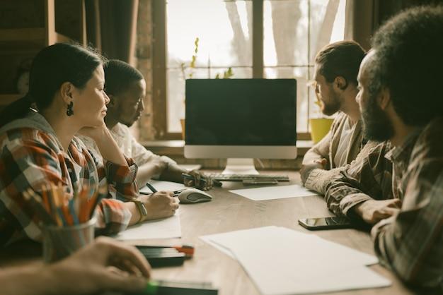 Trabajo en equipo de jóvenes profesionales independientes en el soleado espacio de coworking