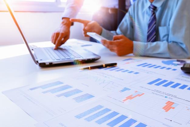 Trabajo en equipo de negocios discutiendo ideas y planeando sobre el resumen de ganancias en la sala de reuniones.