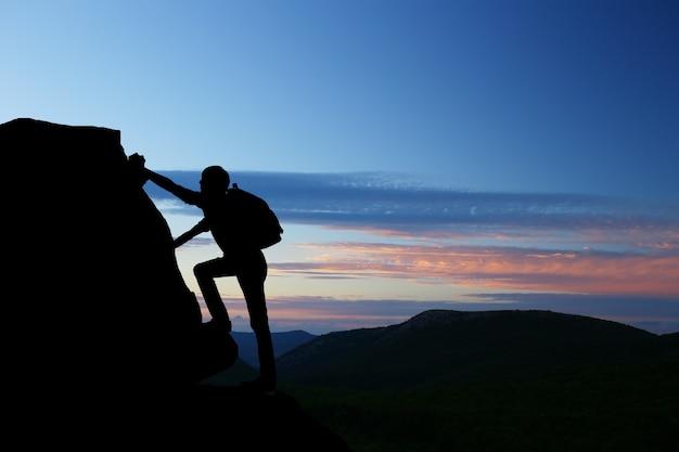 El trabajo en equipo pareja senderismo se ayudan mutuamente a confiar en la silueta de asistencia en las montañas, puesta de sol. trabajo en equipo de excursionista hombre y mujer ayudando mutuamente en la cima del equipo de escalada