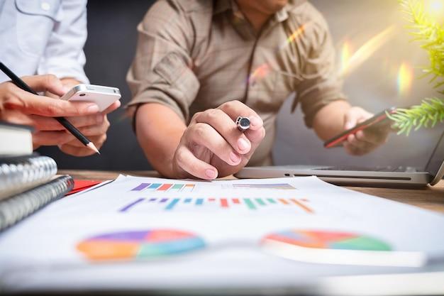 El trabajo en equipo del proyecto empresarial planifica un nuevo proyecto de puesta en marcha, reunión de gerentes de finanzas, teléfono inteligente con diseño de computadora con pantalla de acoplamiento de tableta digital, a la luz de la mañana.