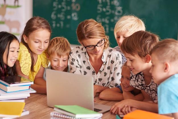 Trabajo en equipo sobre el portátil del profesor