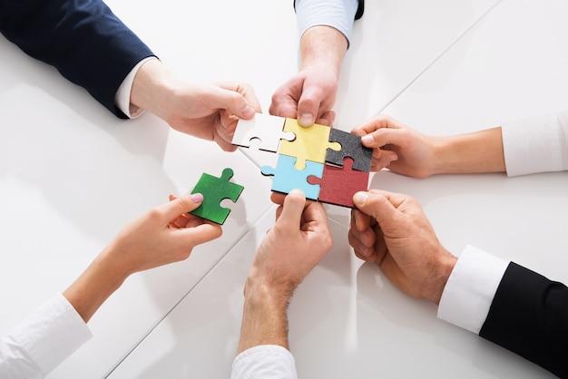 Trabajo en equipo de socios concepto de integración y puesta en marcha con piezas de rompecabezas