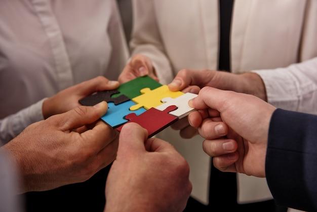 Trabajo en equipo de socios. concepto de integración y puesta en marcha con piezas de rompecabezas