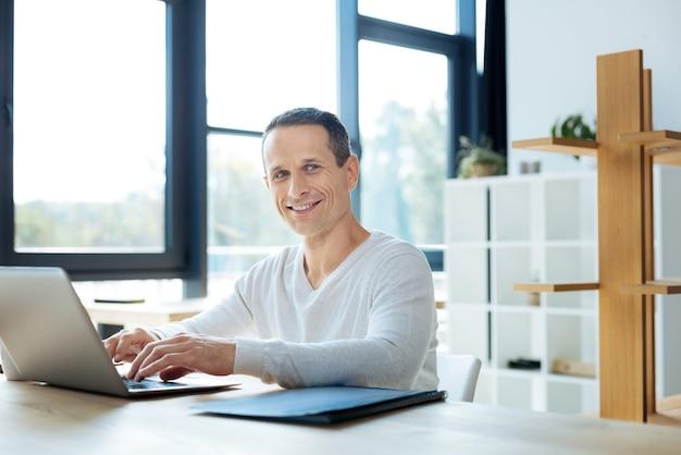 Trabajo favorito. alegre hombre de negocios encantado positivo escribiendo en la computadora portátil y sonriendo mientras disfruta de su trabajo