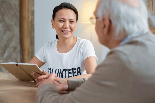 Trabajo favorito. bonito voluntario satisfecho sonriendo mientras lleva el cuaderno y mirando al hombre mayor