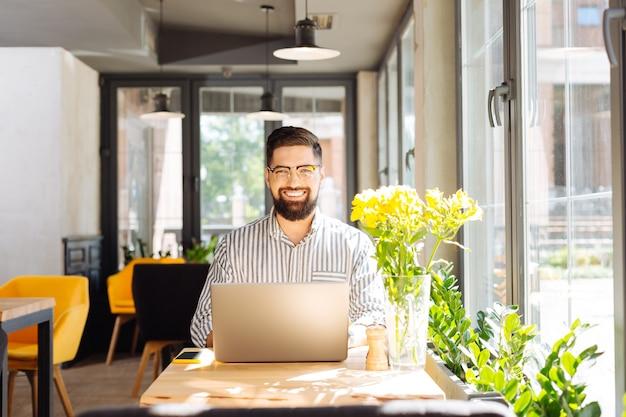 Trabajo favorito. hombre barbudo feliz sentado a la mesa en el café mientras disfruta de su trabajo