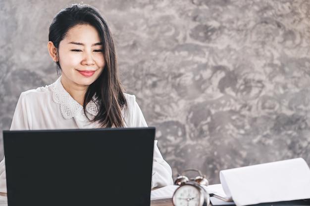 Trabajo feliz asiático de la mujer de negocios en el ordenador