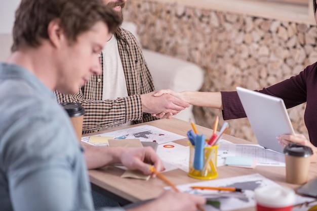 En el trabajo. gente agradable, agradable y encantada sentada en la mesa y dándose la mano mientras se conocen