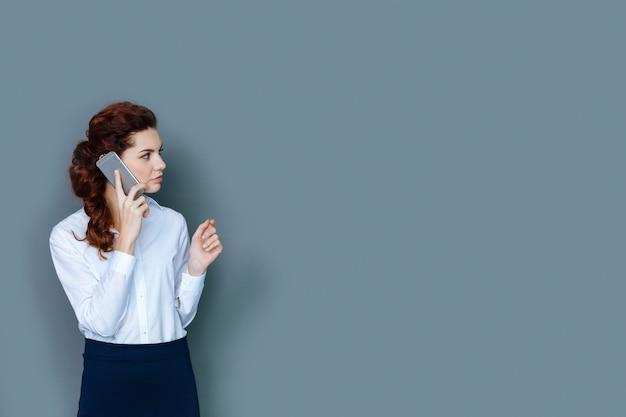 En el trabajo. grave empresaria segura agradable poniendo un teléfono en su oído y haciendo una llamada mientras está en el trabajo