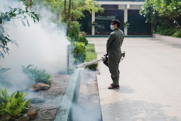 El trabajo del hombre se empaña para eliminar el mosquito y prevenir la propagación de la fiebre del dengue y el virus zika