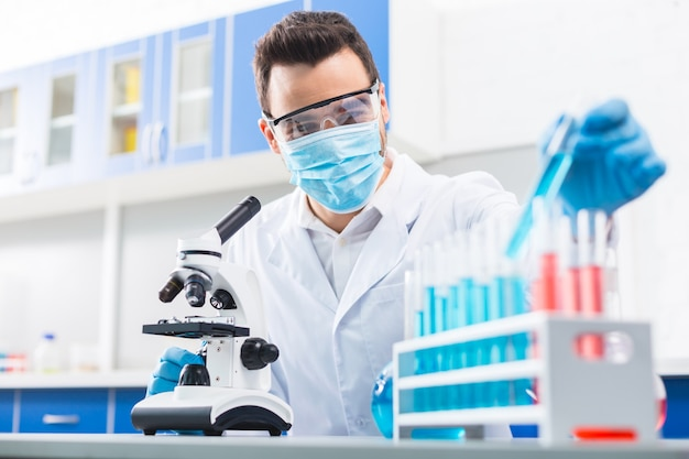 Trabajo incómodo. asistente de laboratorio masculino hábil profesional que usa reactivo mientras realiza el experimento y toca el microscopio