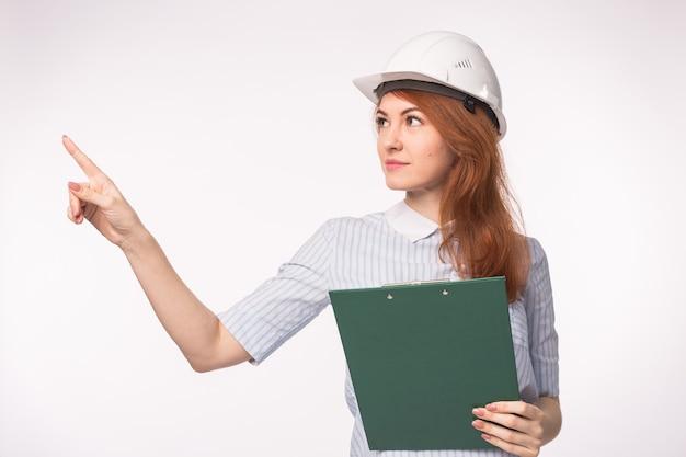 Trabajo, ingeniería, concepto de personas - joven hermosa pelirroja en casco de arquitecto.